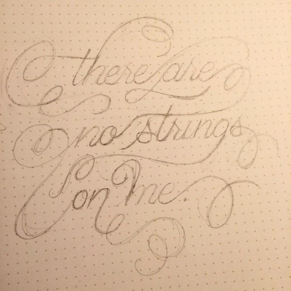 "Pencil sketch on dot-grid paper of italicized Copperplate-esque script with swashes linking the words together, reading ""there are no strings on me."""
