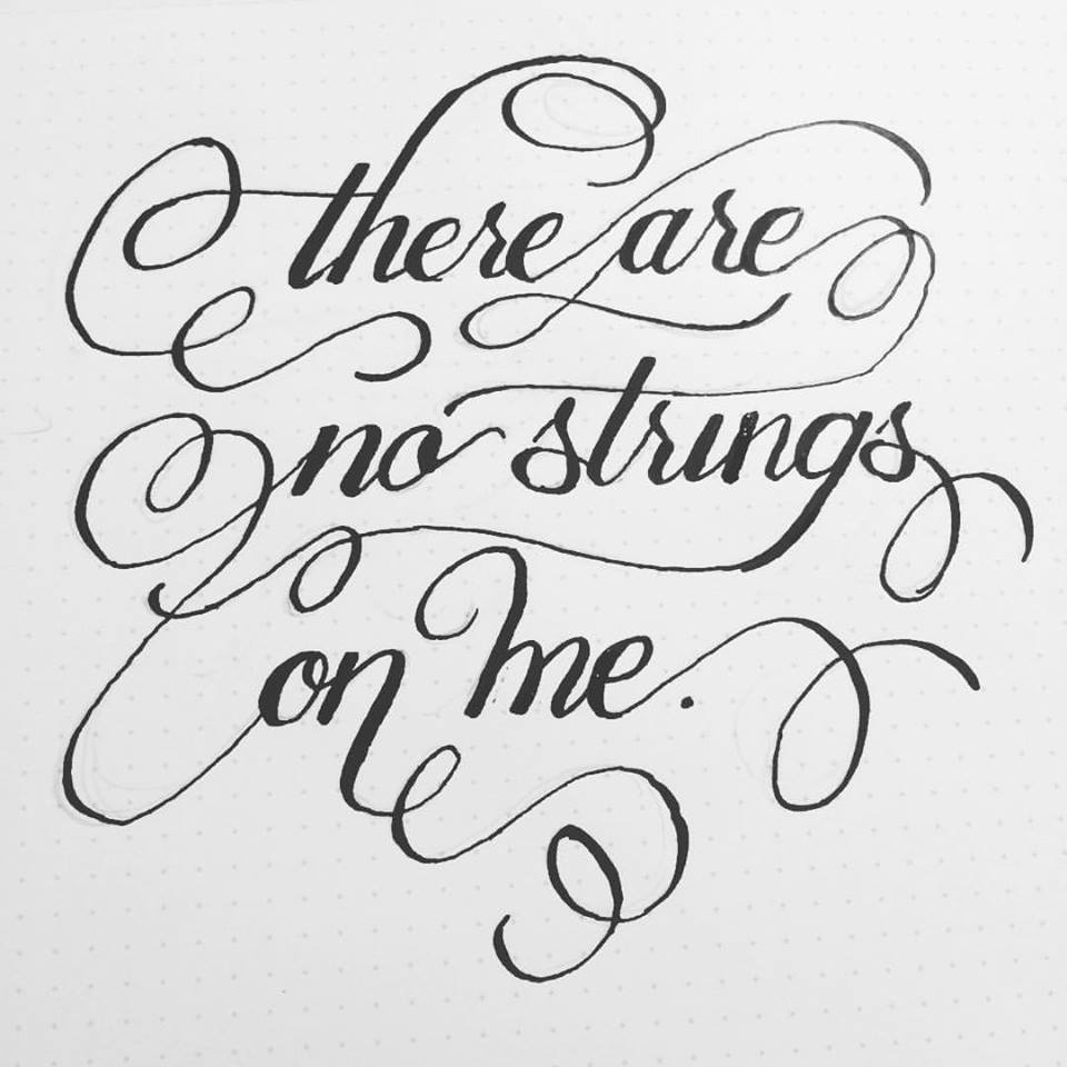 "Inked calligraphy on dot-grid paper of italicized Copperplate-esque script with swashes linking the words together, reading ""there are no strings on me."""