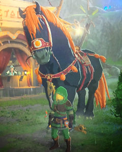 Screenshot from The Legend of Zelda: Breath of the Wild. The main focus is of a very large black horse with orange mane and tail, with Link (the main character) standing in front of the horse. The horse is so tall that Link is only as tall as the horse's legs.